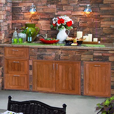 Pacific Teak Millworks outdoor kitchen storage in a stone bbq island
